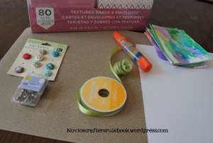 The Materials: Blank card, brads, glue, cardstock, yarn or ribbon, pen